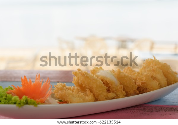 Deep batter fried squid rings calamari on vintage wood table with blurred white beach background