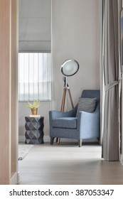 Deep blue armchair with stylish standing lamp in the corner of living room