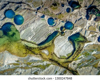 Deep blue colours ofrock pools and lighter aqua yellows of the shallower pools aerial view of exposed coastal rock shelf which is textured with cracks and weathered patterns
