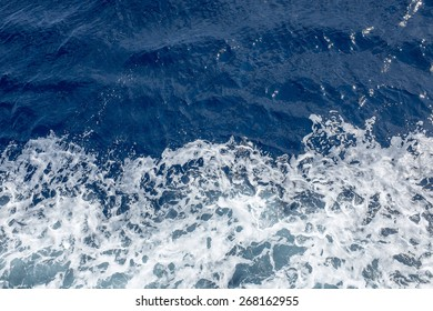 Deep blue ocean with foam on the surface