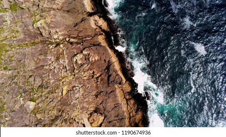 Deep blue ocean water and steep cliffs from above