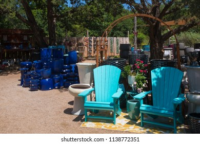 deep blue pots and two lounge chairs all for sale at a nursery