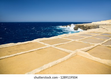 Deep blue sea, horizon and sky with yellow-brown sand stone shore foreground. Salt ponds in Gozo island, Malta.
