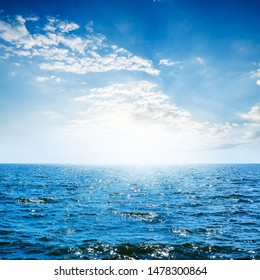 deep blue sea and sky with clouds in sunset time