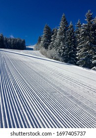 Deep blue sky on a sunny winter day in the ski resort of Les Gets and the freshly pisted corduroy piste on Mont Chery is ready for the day's skiers