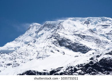 Deep blue sky and wind blowing away snow from the peak of a snow capped mountain, Nepal, Himalayas, Annapurna Circuit