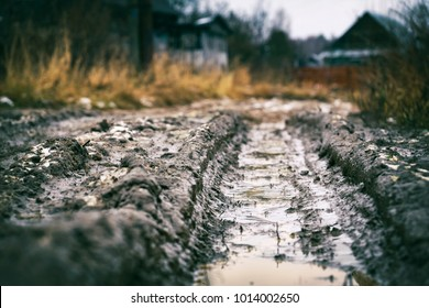 Deep car rut on russian dirt road in winter thaw