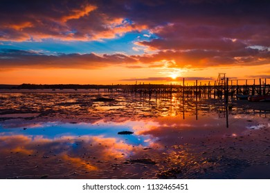 Deep colours of orange and red in the skies over a Poole Harbour jetty near Sandbanks