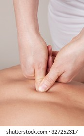 Deep connective tissue massage on a woman's shoulder blade
