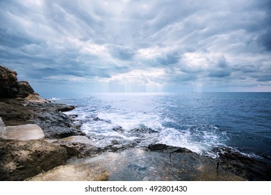 Deep dark blue sea waves breaking on a rocks forming a sea foam. Sea waves near cliff. White foam of a sea wave. The strong waves of the sea before the storm, Cape Tarkhankut, Crimea, Russia