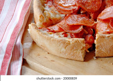 Deep dish pepperoni pizza with a red and white striped dish towel.