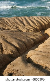 Deep eroded gullies transitioning abruptly to a stormy sea.