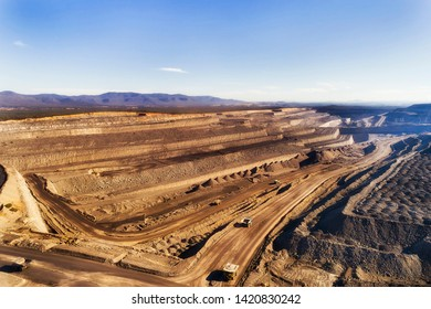 Deep exhavation of fossil fuel minerals from open cut black coal mine in Hunter Valley coal basin of Australia with industrial machinery, trucks and excavators moving resources.