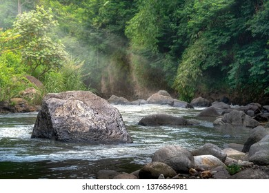 Deep Forest Stream Water Rushing by Big Rock in Middle River at Morning Sunshine and Warm Sunbeam or Sun Ray Through Tropical Forest Tree. Concept of Divine Harmony with Environment