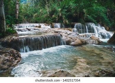 Deep forest waterfall at Erawan waterfall National Park. long exposure. Beautiful scenery. Waterfall in the wild jungle. Asian nature. Cascade of small waterfalls.
