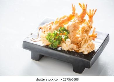 deep fried almond shrimp tempura on black plate