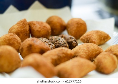 Deep fried Brazilian croquettes draining on a paper towel (coxinha, kibbe, risole)