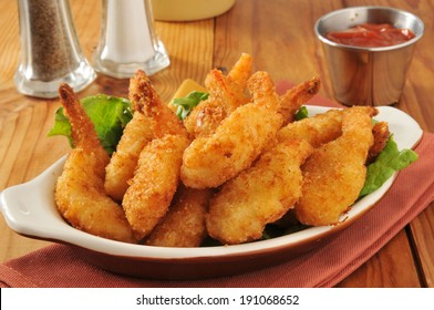 Deep fried butterfly shrimp in a bowl with cocktail sauce