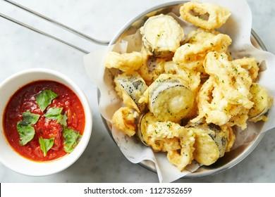 Deep fried calamari and sushi roll with tomato sauce
