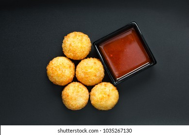 Deep fried cheese  and potato balls with sauce, top view on the black background
