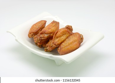 Deep fried chicken wing with fish sauce on white plate and white background.