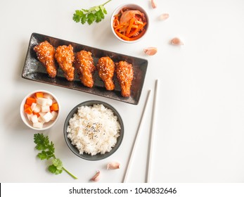 Deep fried chicken wing plate with garlic sauce in Korean style serve with rice, kimchi and pickled radish on white background in top view with copy space  for asian food concept.