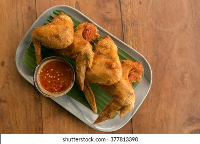 Deep fried chicken wings crispy and delicious thai sweet sauce on a wood table