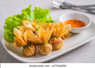 Deep fried crispy wonton, money bag or golden bag (Toong Thong) served with sweet chilli sauce, Thai food culture