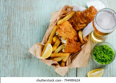 Deep fried fish and chips in combination with lemon slices, green peas and beer on a rustic table. Feed your tummy with yummy food.