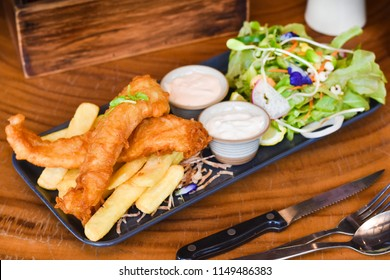 Deep fried Fish and Chips with Tartar sauce, mayonnaise and Vegetable on Ceramic plate