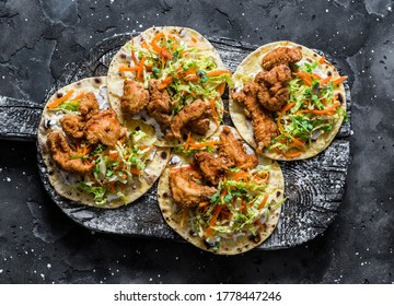 Deep fried fish and coleslaw salad tacos on a cutting board on dark background, top view
