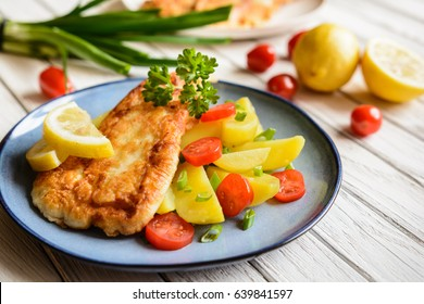 Deep fried fish fillets in batter, served with potato, tomato and scallion