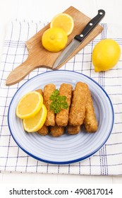 deep fried fish finger made from alaska pollock fish with slice lemon and parsley on a plate