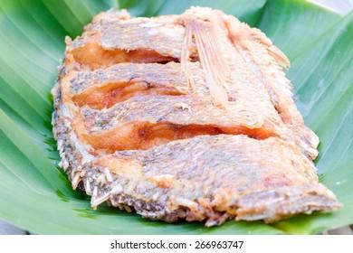 deep fried fish on green banana leaf