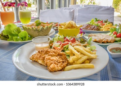 Deep fried fish steak served with french fries and fresh vegetables on plate , And  full of food on table