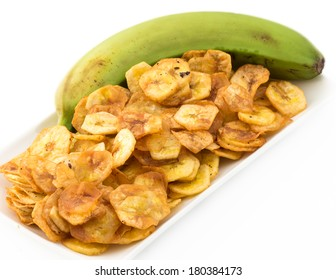 Deep fried green banana chips over a white background