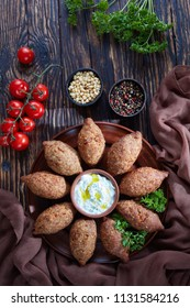 deep fried kibbeh of ground beef meat mixed with bulgur, fried minced meat with pine nuts, spices, garlic and herbs on a clay plate on an old dark wooden table, vertical view from above