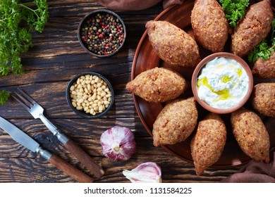 deep fried kibbeh of ground beef meat mixed with bulgur, stuffed with fried minced meat with pine nuts, spices, garlic and herbs on a clay plate on an old dark wooden table, close-up, flat lay