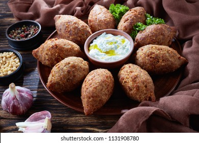 deep fried kibbeh of ground beef meat mixed with bulgur, stuffed with fried minced meat with pine nuts, spices, garlic and herbs on a clay plate on an old dark wooden table, close-up