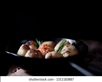 Deep fried mozzarella and rice balls with rosemary herb garnish in a black wrought iron skillet shot against black with generous accommodation for copy space.
