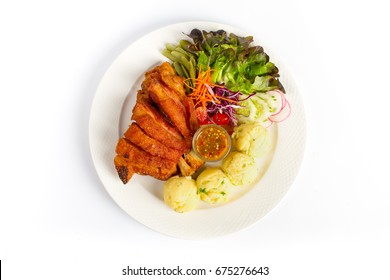 Deep fried pork knuckle with mashed potatoes, salad and spicy sauce on white background