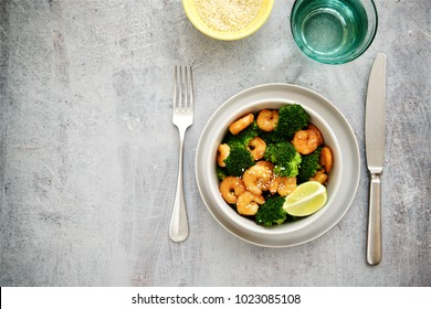 Deep fried shrimp with broccoli and sesame seeds. Light background, empty space