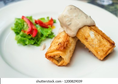 Deep fried shrimp and zucchini rolls with hollandaise sauce (selective focus)