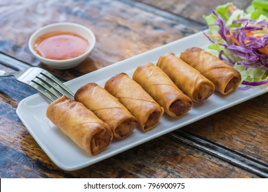 Deep fried spring rolls and vegetables on plate