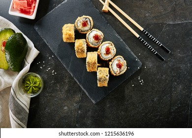 Deep Fried Sushi Rolls with Salmon and Philadelphia Cream Cheese Top View. Hot Crispy Tempura Maki Set with Tuna Fish and Nori Seaweed on Natural Black Stone Slate Background with Copyspace