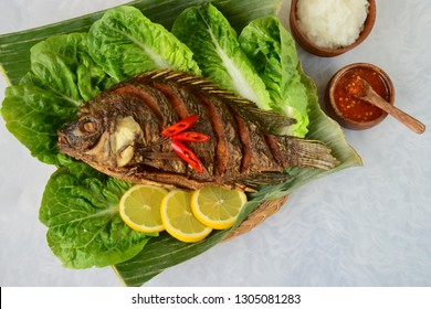 Deep fried Tilapia fish on lettuce garnish with lemon and chili. Served with rice, sliced cucumber, tomato and Sambal or chili sauce