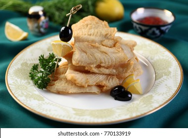 Deep fried walleye on a plate with lemon and olives.