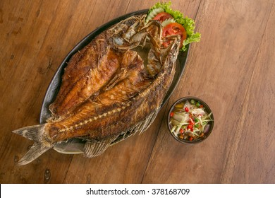 Deep fried whole fish crispy and delicious spicy sauce on a wood table - asian cuisine