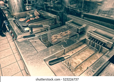 Deep fryers and grill, equipment of a fast food restaurant, toned image