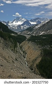 Deep mountain valley with snow-capped mountains in background